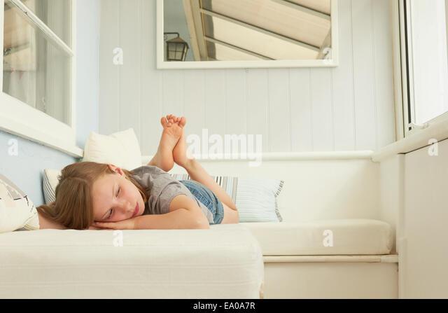 Sullen girl lying on holiday apartment seat - Stock-Bilder