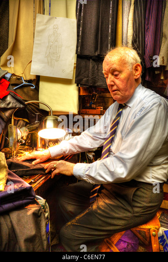Tailor stitching a suit at work on his singer sewing machine old man working to make ends meet, tailoring - Stock Image