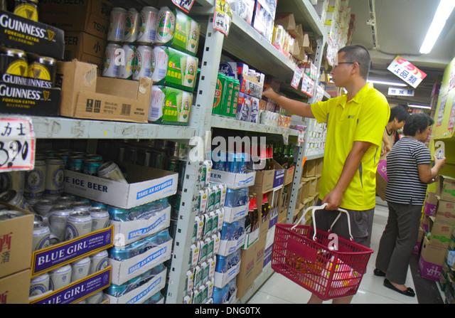 Hong Kong China Kowloon Sham Shui Po shopping grocery store supermarket sale display shelves Asian man aisle beer - Stock Image