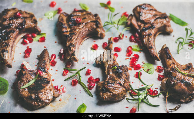 Grilled lamb ribs with pomegranate seeds, fresh mint and rosemary over metal baking tray background, selective focus, - Stock Image