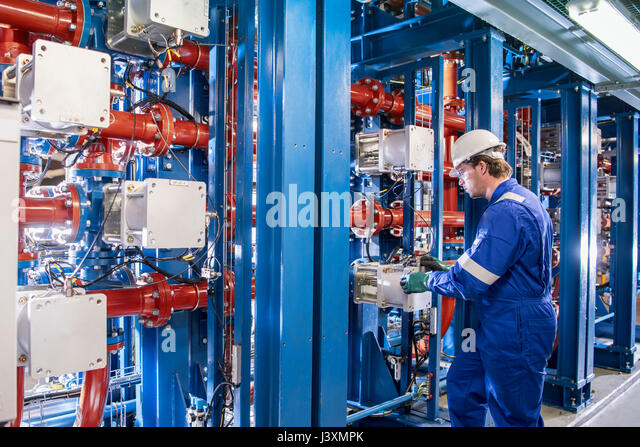 Worker with process machinery in oil blending factory - Stock Image