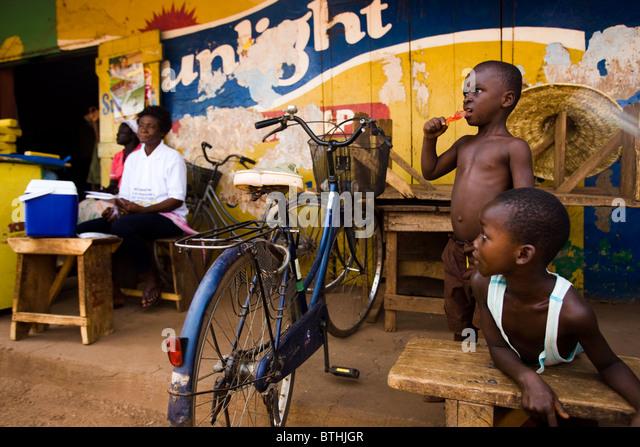 A health worker sits waiting for mothers to bring their children for vaccination in a commercial area of Salaga, - Stock Image