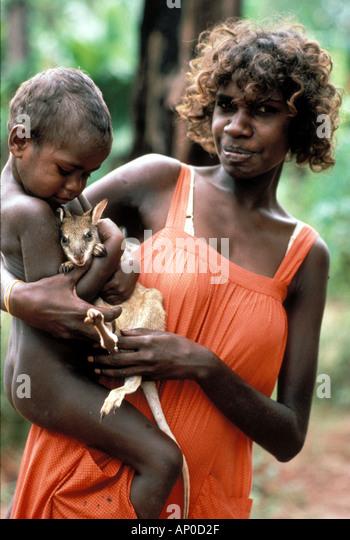 Aboriginal woman with her child cuddling pet baby kangaroo whose mother killed for food Arnhem Land NT Australia - Stock Image