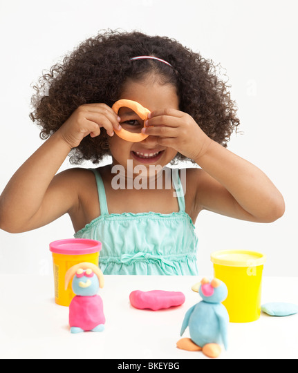 Young girl playing with clay - Stock Image