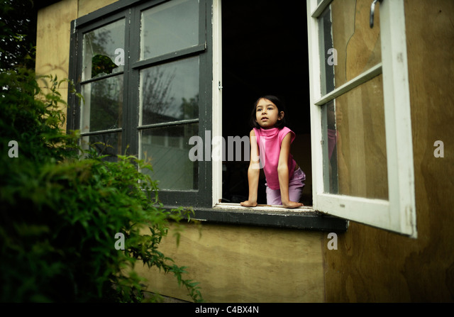 Girl looking out shed window - Stock Image
