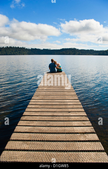 Couple on holiday sitting together at romantic Lake Ianthe, South Island, New Zealand, Pacific - Stock-Bilder