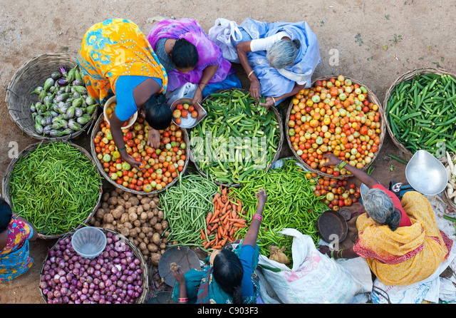 Indian women buy vegetables from a street market in Puttaparthi, India - Stock-Bilder