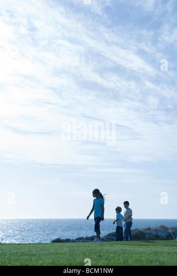 Children standing on grass, ocean horizon in background - Stock Image