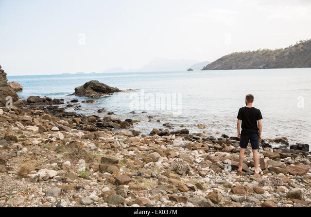 Man looking out from coastline at Phaselis, Lycian way, Turkey - Stock Image