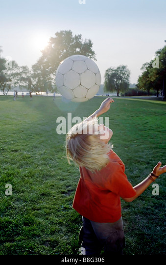 Blonde Boy doing a Header - Soccer - Leisure Time - Youth - Meadow - Stock Image
