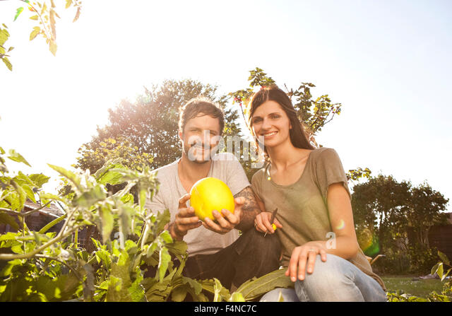 Smiling couple with yellow courgette in the garden - Stock Image