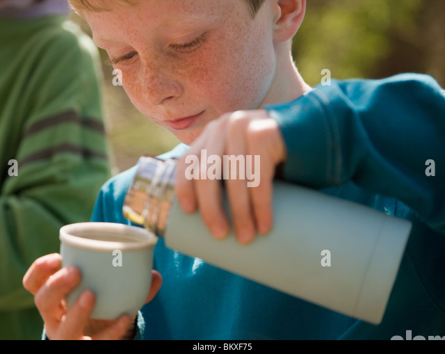 Close up of young boy pouring water from insulated flask - Stock Image
