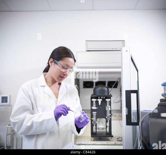 Scientist putting liquid in beaker - Stock Image