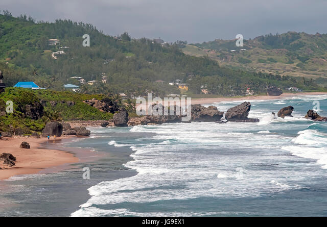 View of dramatic Atlantic east coast with line of boulders going into the ocean at Bathsheba Barbados - Stock Image