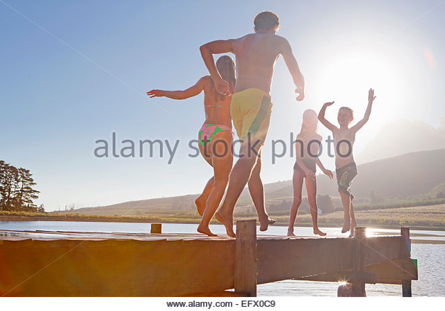 Happy family running and jumping on jetty - Stock-Bilder