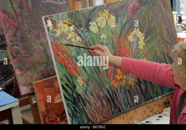 Virginia Alexandria Old Town Alexandria Torpedo Factory Art Center artist in residence painting flowers senior woman - Stock Image