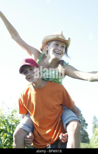 teen boy giving teen girl piggyback ride - Stock Image
