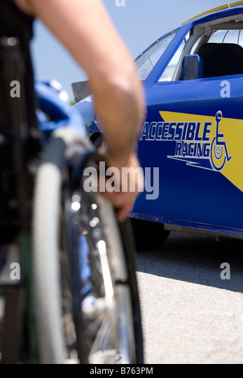 Person on wheelchair approaching to racing car, close-up - Stock Image