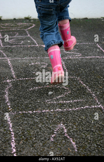 Girl jumps playing hopscotch - Stock Image