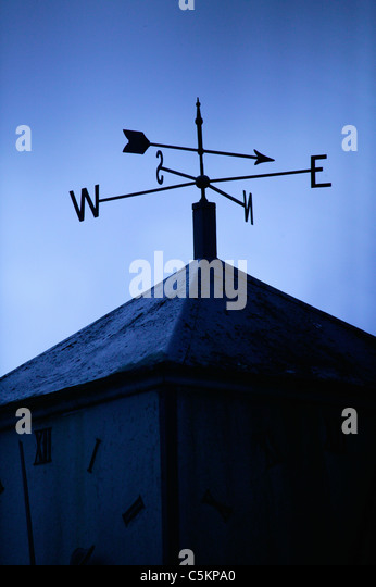 A weather vane on the roof of a building, pointing North-East, silhoutted against a blue sky - Stock Image