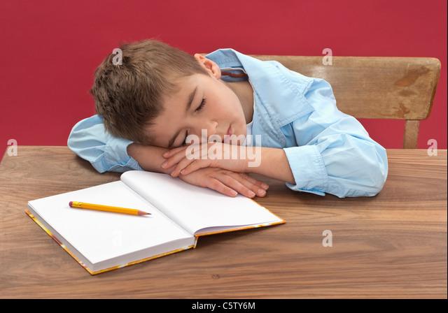 Schoolboy (6-7) sleeping at desk - Stock Image