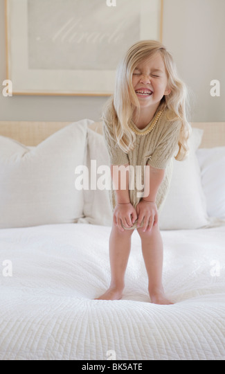 Girl with big smile standing on bed - Stock Image