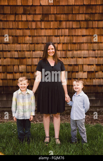 Mom with two kids, both boys, in a lifestyle portrait outdoors. - Stock Image