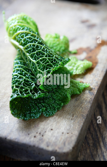 Curly cabbage leaf on a chopping board - Stock Image