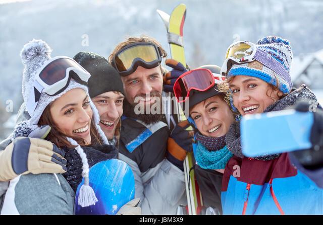 Smiling skier friends taking selfie with camera phone - Stock-Bilder
