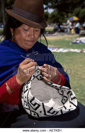 Ecuador Quito Alameda Parc park Sunday Open Market Cotopaxi female sells arts and crafts weaves basket hat - Stock Image