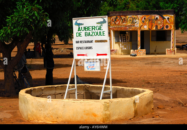 Community based pro poor tourism initiative, sign for accommodation facilities and souvenir stall Bazoule Burkina - Stock Image