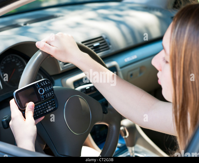 Teenage girl texting on cell phone while driving - Stock Image