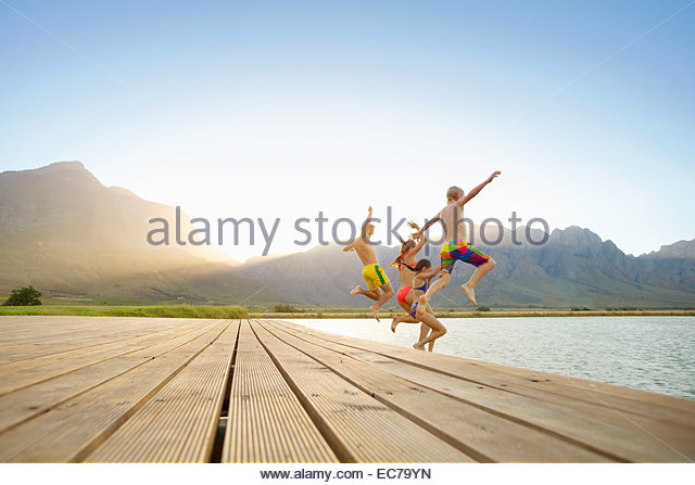 Family, in swimwear, jumping into a lake from a jetty - Stock-Bilder