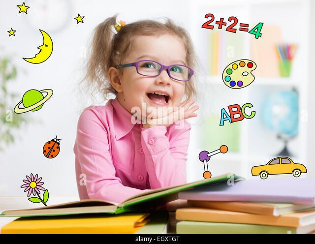 Funny smart kid in glasses reading book in kindergarten - Stock Image