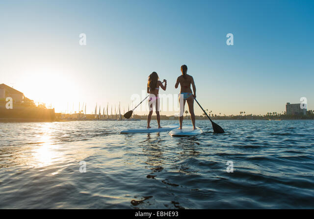 Rear view of two women stand up paddleboarding, Mission Bay, San Diego, California, USA - Stock Image
