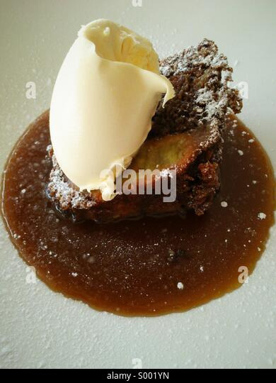 Pear and ginger cake with clotted cream and toffee sauce. - Stock Image