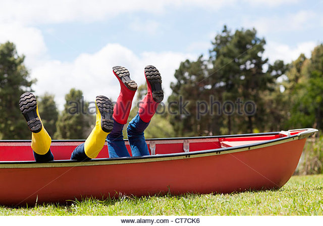 Brother and sister in canoe with legs in the air - Stock Image