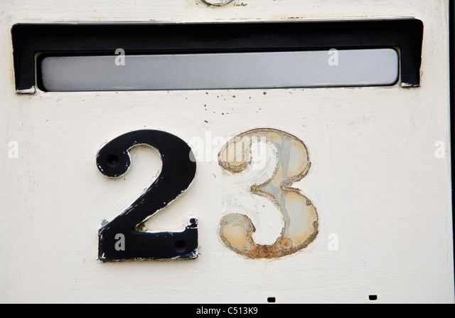 Street address on wall beneath mail slot, one number missing - Stock Image