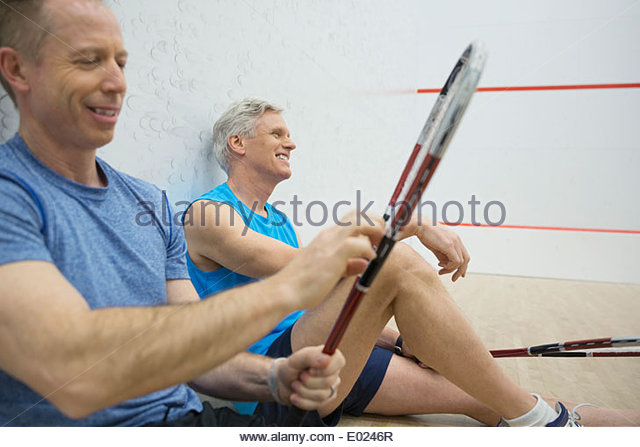 Men resting on squash court - Stock Image