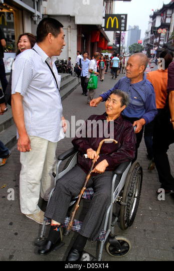 Shanghai China Huangpu District Yuyuan Garden Fuyou Road shopping market marketplace Asian man woman disabled wheelchair - Stock Image