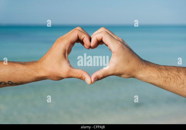 Two men's hands forming heart shape by ocean, cropped - Stock-Bilder