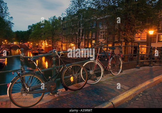 Amsterdam briudge over canal at twilight bicycles - Stock Image