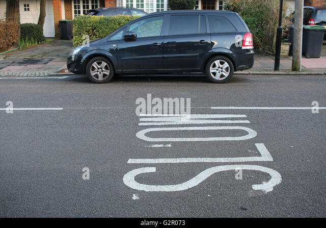 Slow road markings against a Vauxhall Zafira minivan, houses - Stock Image