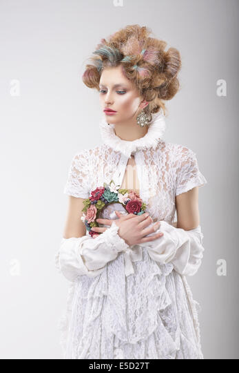 Personality. Luxurious Woman with Flowers in Evening Costume - Stock Image