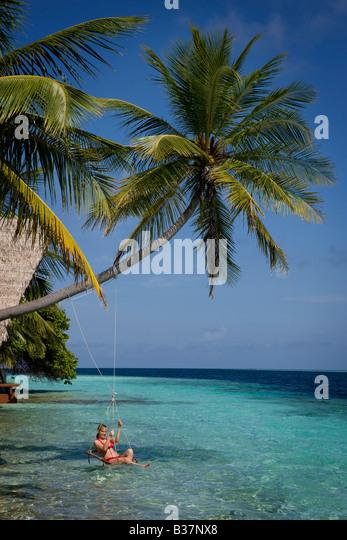 Girl swinging on rope swing on South Ari Atoll in Maldives near India - Stock-Bilder