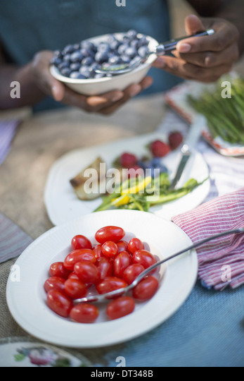 Parents and children helping themselves to fresh fruits and vegetables - Stock Image