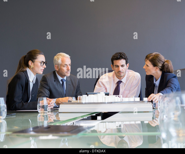 Business people looking at architectural model in office - Stock Image