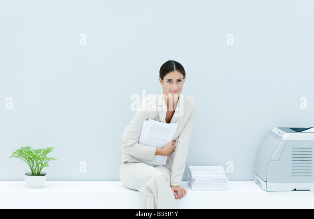 Young professional woman sitting on ledge with legs crossed, holding documents and smiling at camera - Stock-Bilder