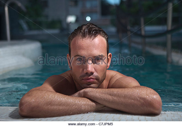 Man resting on edge of swimming pool - Stock Image