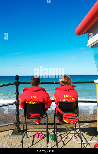 two RNLI female lifeguards sitting looking out to the Norfolk coast on a summers days - Stock Image